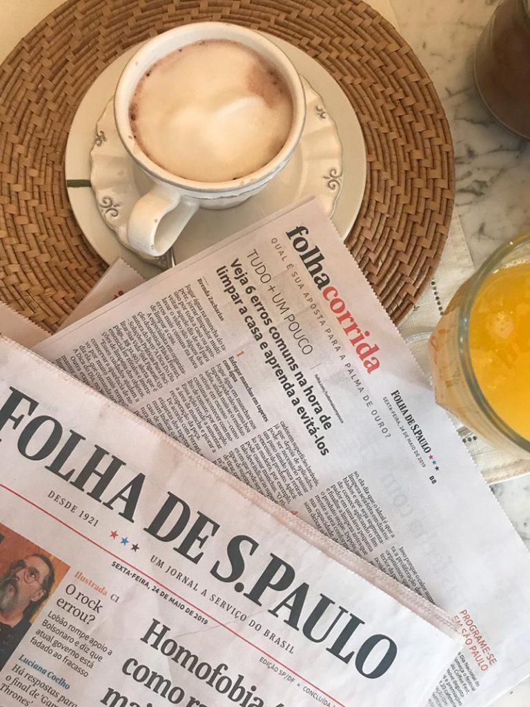 Foto do jornal Folha de S.Paulo em cima de uma mesa com um café e um copo de suco de laranja.