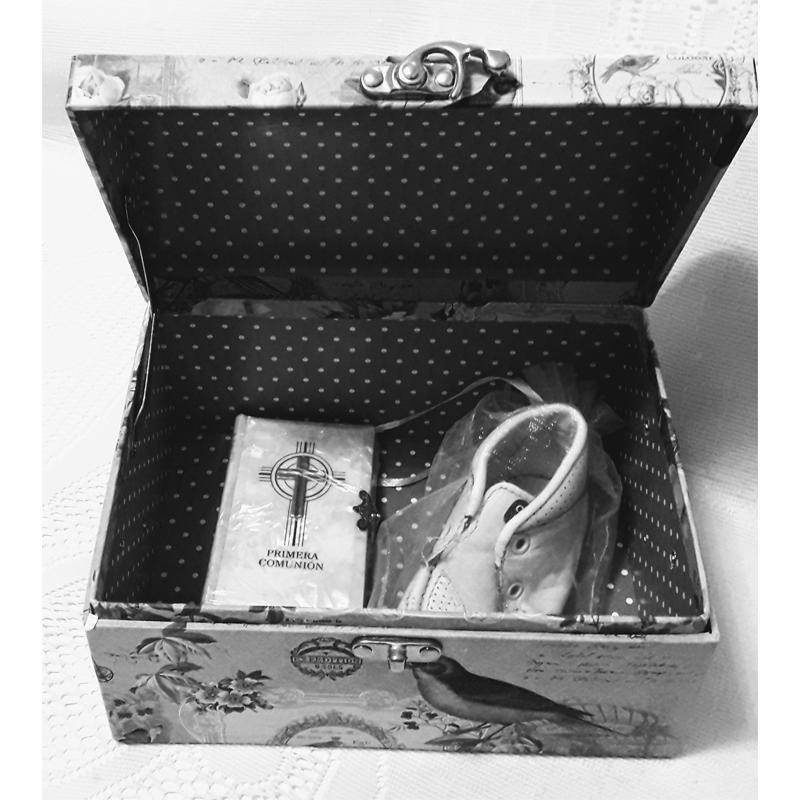 Imagem de uma caixa aberta com um sapatinho e um livro dentro.