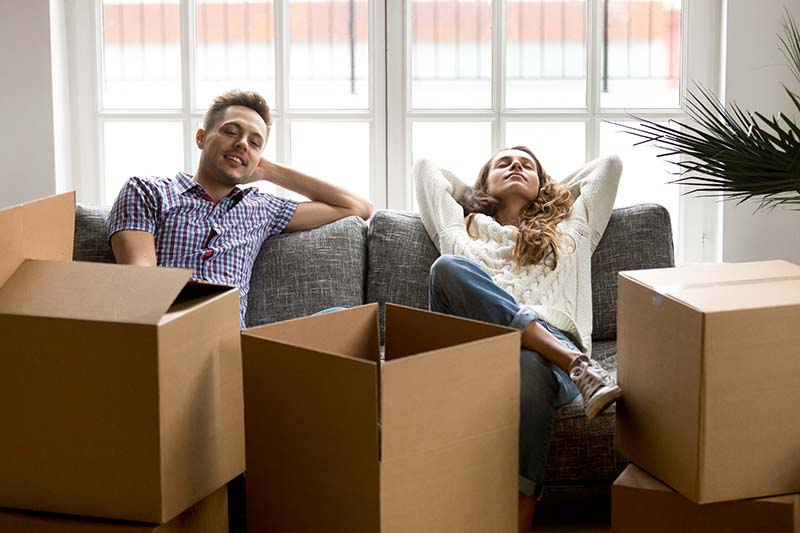 Happy couple relaxing on couch after moving in new home, smiling young husband and wife homeowners or tenants taking break for rest together while packing unpacking cardboard boxes relocating concept